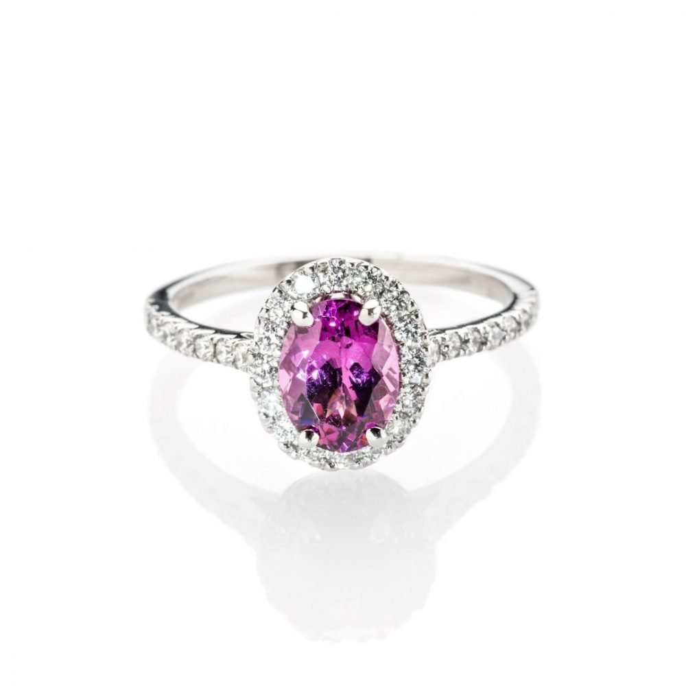 A beautiful pinkish oval Rhodalite Garnet is surrounded by Diamonds in this oval cluster ring makes a gorgeous January birthstone gift.